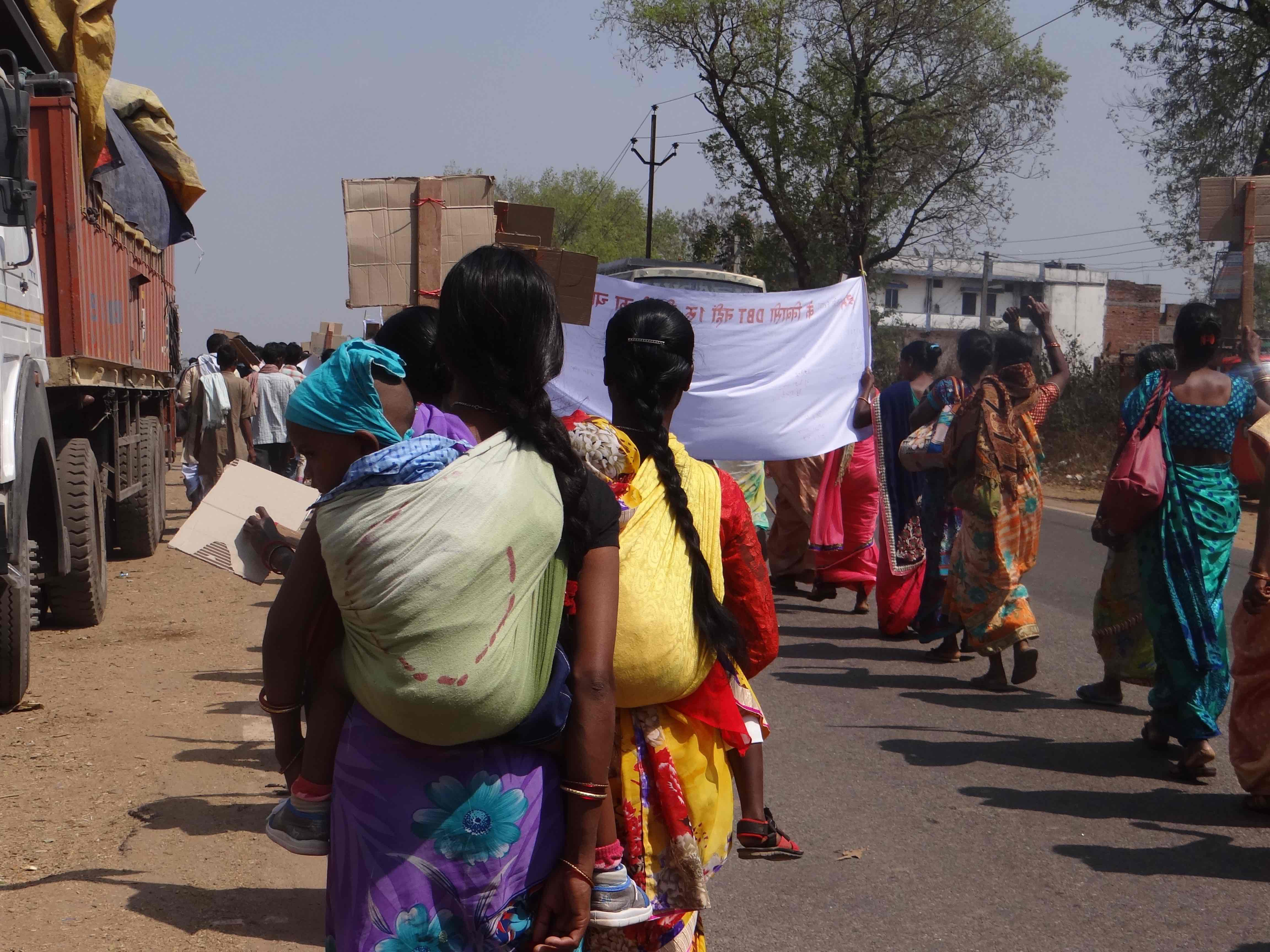 Women participate in the 8 km march against the DBT scheme, carrying their children on their backs. Credit: Jahnavi Sen