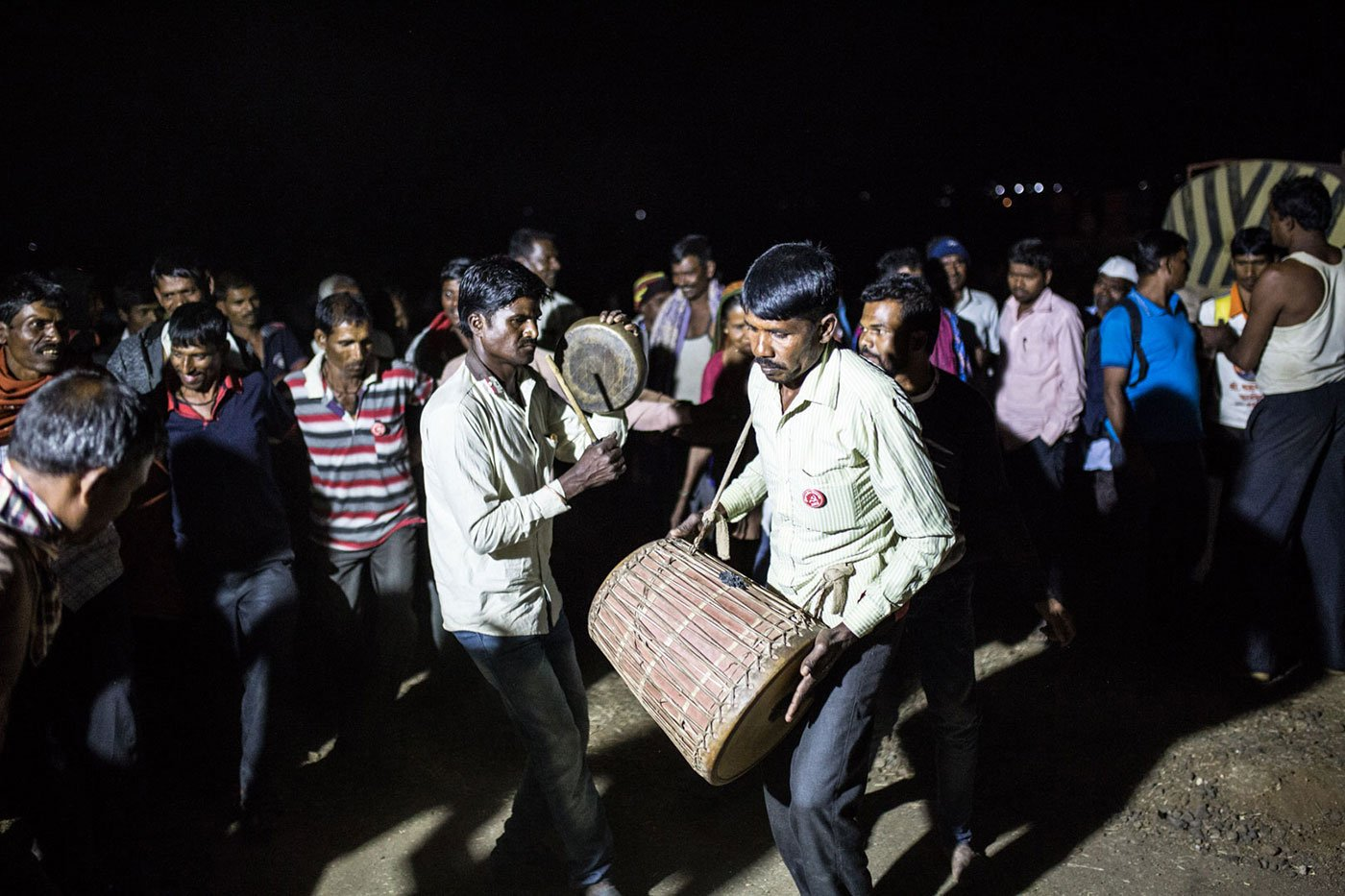 After a long day of walking, some farmers sing and dance at night; others like Waghere are exhausted; soon, everyone rests for the night under the open sky. Credit: Shrirang Swarge/People's Archive of Rural India