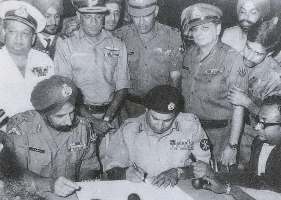 Lieutenant-General A. A. K. Niazi, the commander of Pakistan Eastern Command, signing the instrument of surrender in Dhaka on 16 Dec 1971, in the presence of India's Lt. Gen. Jagjit Singh Aurora. Credit: Wikimedia Commons