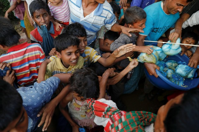 Refugee children scuffle over free meals given away during a wedding party for Rohingya refugees Saddam Hussein, 23, and Shofika Begum, 18, at the Kutupalong camp near Cox's Bazar, Bangladesh, December 11, 2017. Credit: Reuters/Damir Sagolj