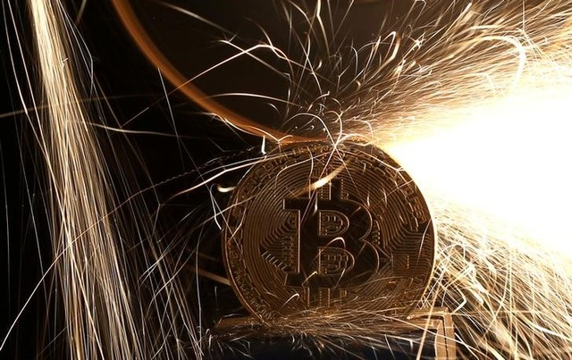 FILE PHOTO: Sparks glow from broken Bitcoin (virtual currency) coins in this illustration picture, December 8, 2017. Credit: Reuters/Dado Ruvic/Illustration/File Photo