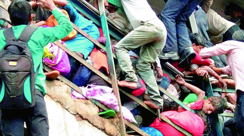 People try to rescue those stuck in the stampede on the Parel-Elphinstone foot over bridge. Credit: PTI/Files