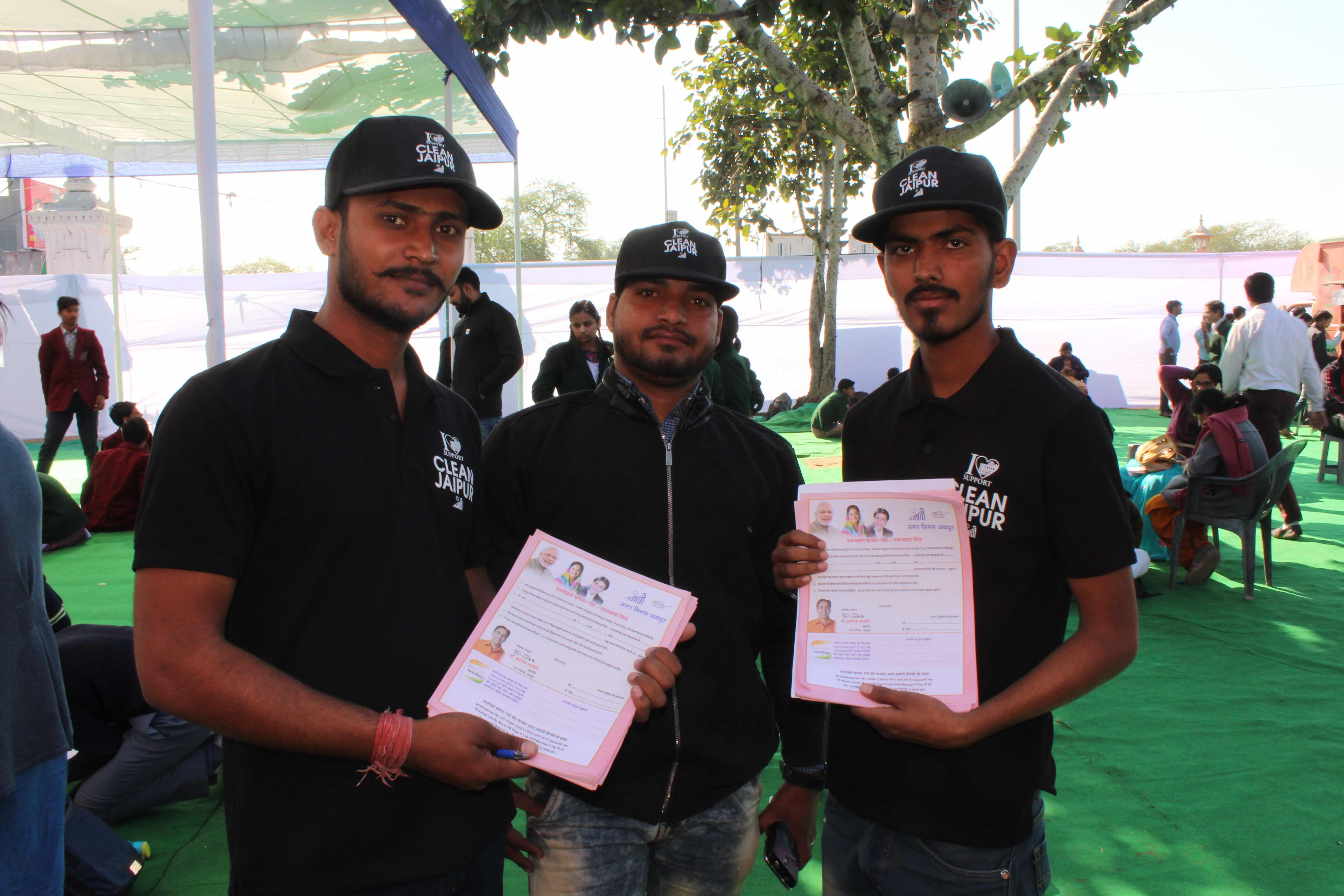 Volunteers hired by the event management company holding up pledge forms. Credit: Shruti Jain
