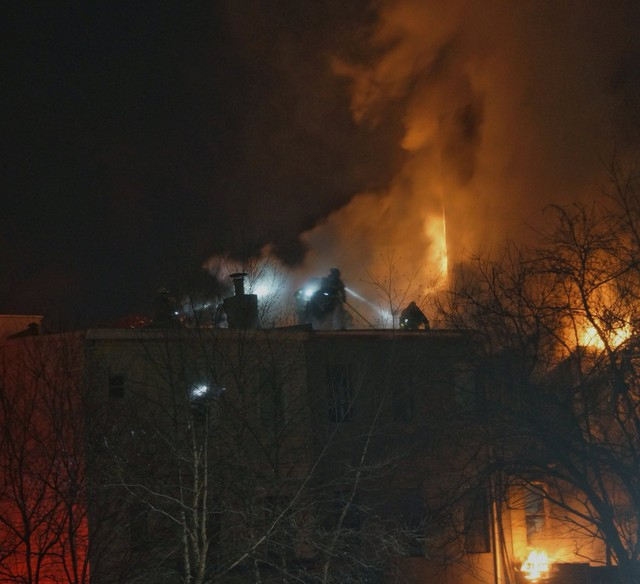 Firefighters are seen on a neighboring building as flames engulf an apartment building in Brooklyn, New York, U.S., in this January 2, 2018 image by Dave Chan obtained from social media. Dave Chan/Social Media/via Reuters