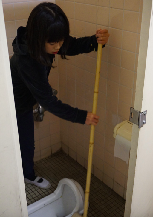 A girl cleaning a toilet at Kita-Yamada Elementary School in Osaka. Credit: Janaki Nair