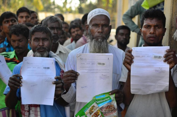 People show their acknowledgment receipts after checking in their names in a draft for NRC. Credit: PTI