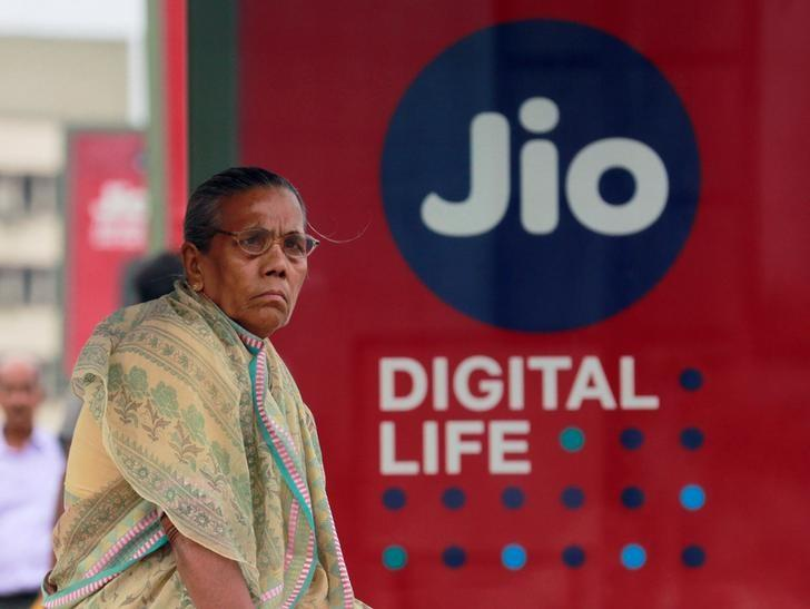 A woman waits at a bus stop with an advertisement of Reliance Industries' Jio telecoms unit in Mumbai, July 11, 2017. Credit: Reuters/Danish Siddiqui