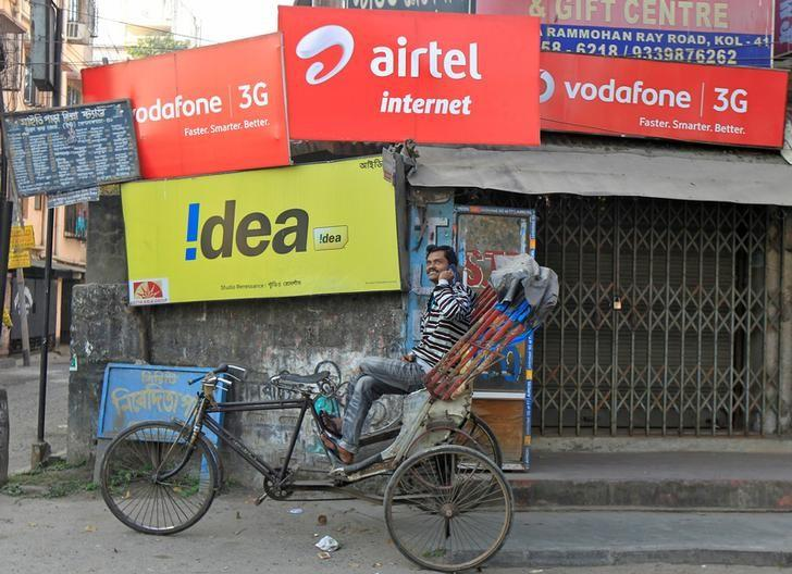 A rickshaw puller speaks on his mobile phone as he waits for customers in front of advertisement billboards belonging to telecom companies in Kolkata, February 3, 2014. Credit: Reuters/Rupak De Chowdhuri/Files