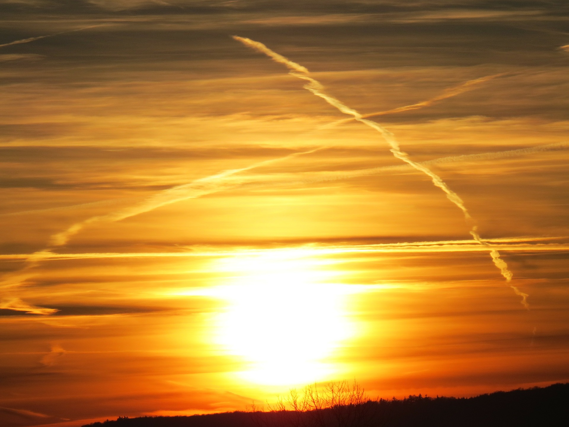 Airplane contrails flank a setting Sun. Credit: Hans/pixabay