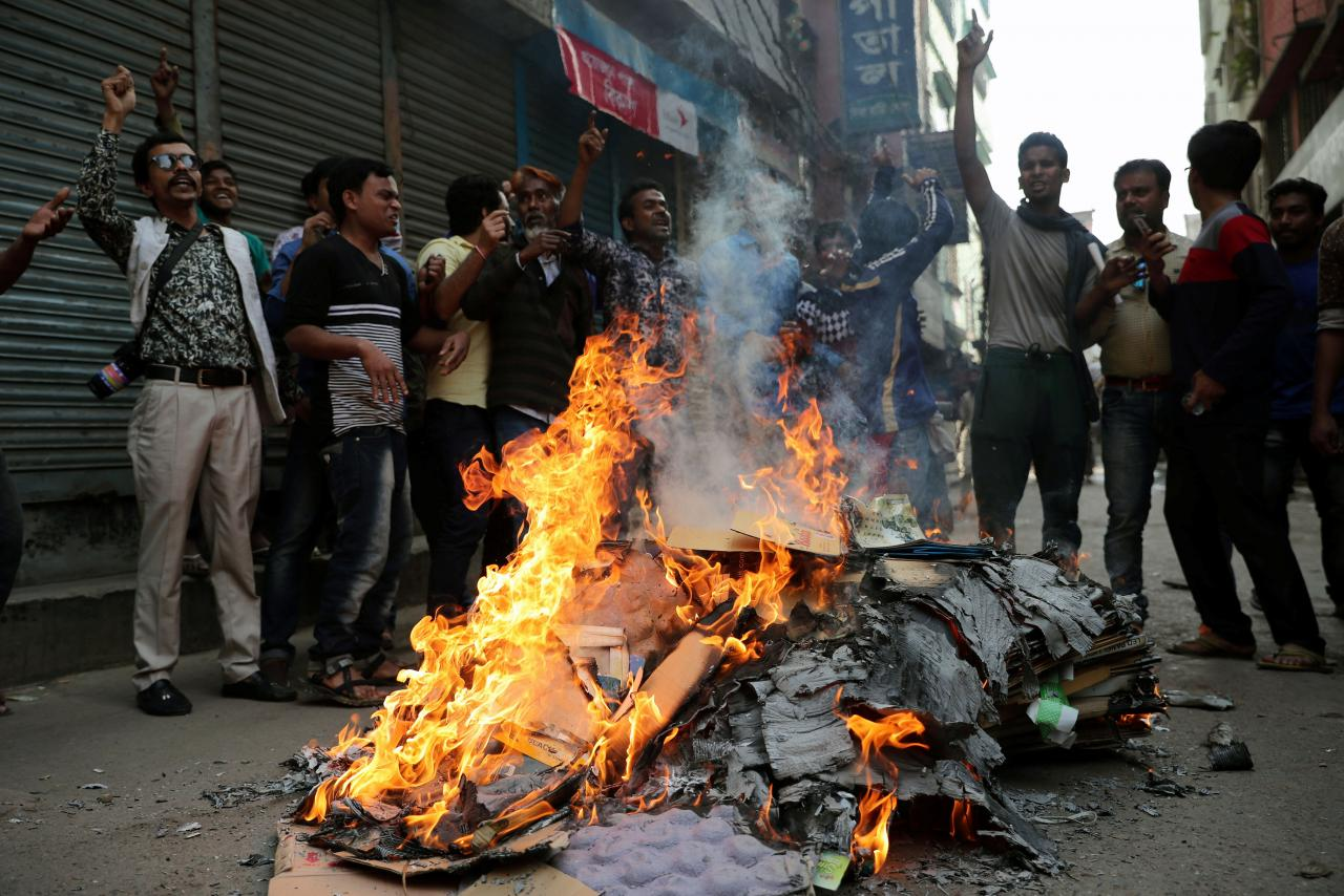 BNP supporters shout slogans as they set fire to posters during a protest in a street in Dhaka, Bangladesh on February 8, 2018. Credit: Reuters/Mohammad Ponir Hossain