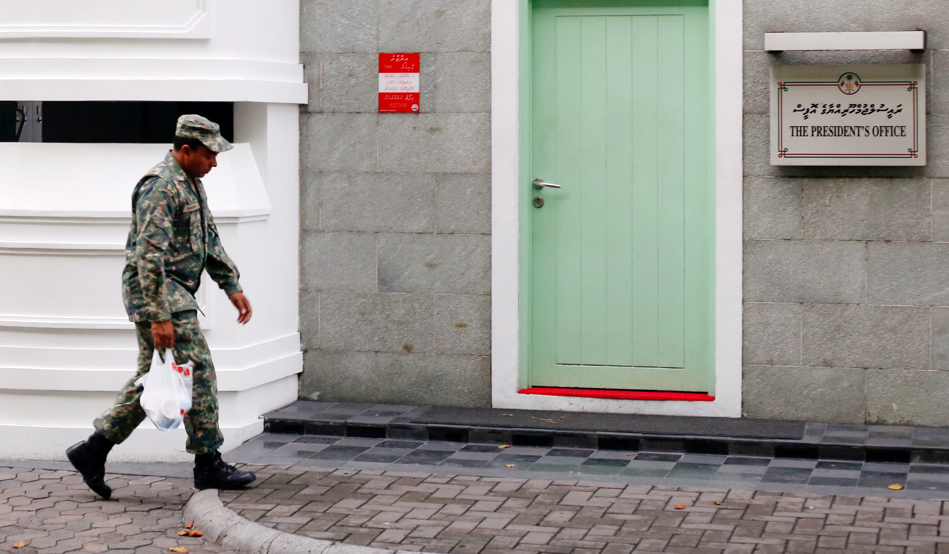 A Maldives National Defence Force soldier walks past the president's office building after Maldives President Abdulla Yameen declared a state of emergency for 15 days, in Male, Maldives February 6, 2018. Credit: Reuters/Stringer