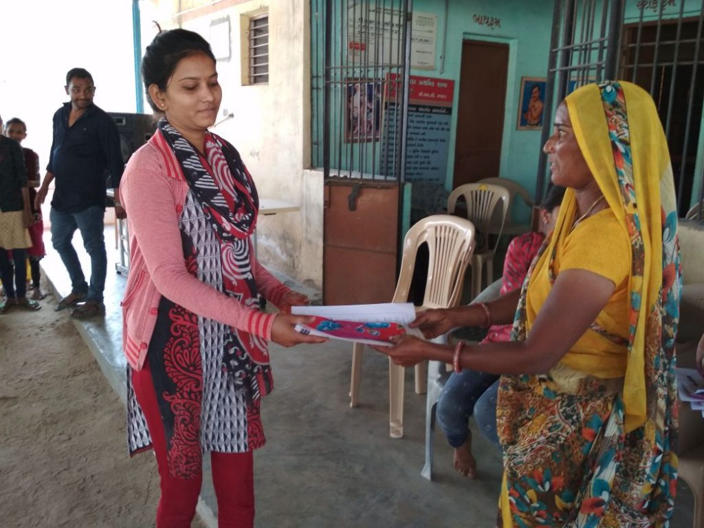 A member of the Vadgam Vikas Samiti presents Manjula Parwar, the sarpanch of Bharkawada, with a sanitary pad. Credit: Priyanka Jain