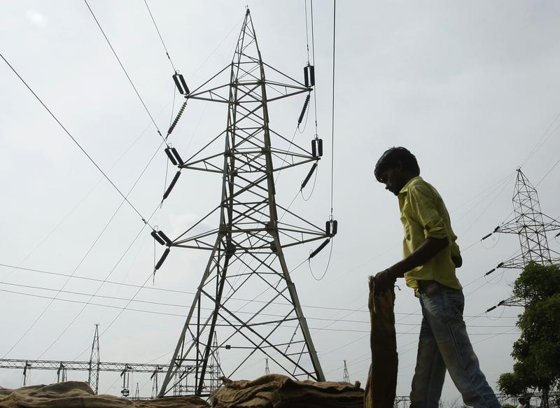 A man stands in front of an electric pylon installed at a power house in the northern Indian city of Allahabad, July 31, 2012. Credit: Reuters/Jitendra Prakash/Files