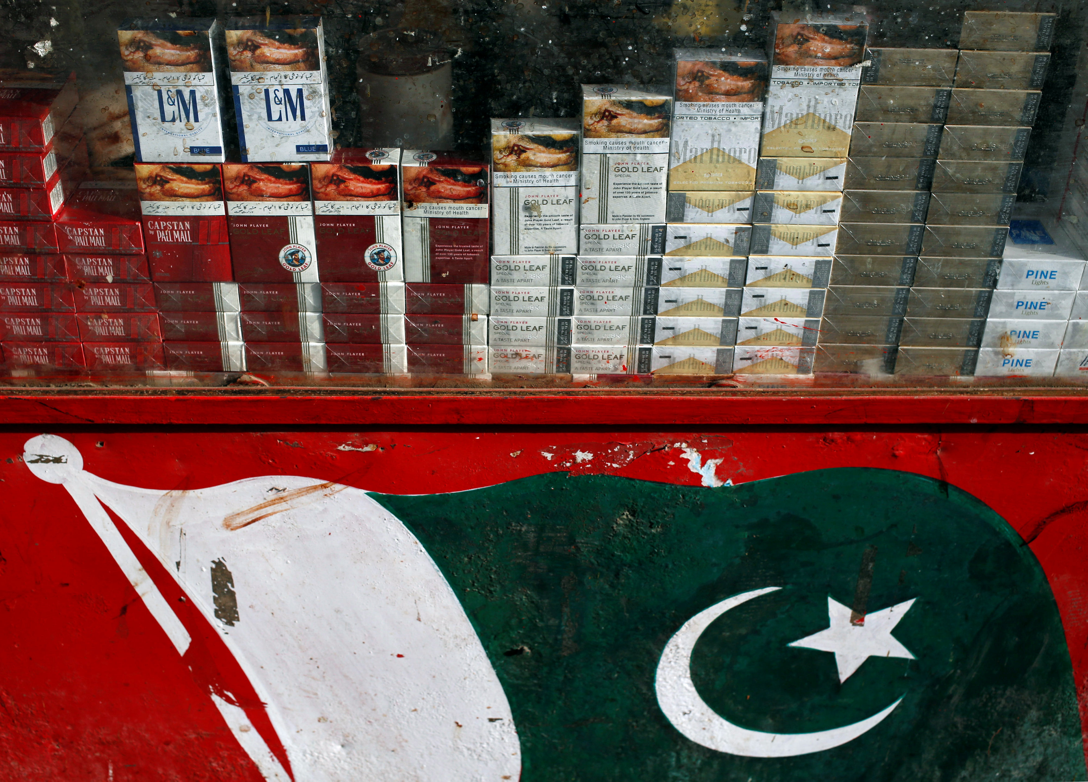 Brands of cigarette packs with health warning are displayed in the showcase of a kiosk painted with Pakistan's national flag, along a road in Karachi, Pakistan May 5, 2018. Credit: Reuters/Akhtar Soomro/Files