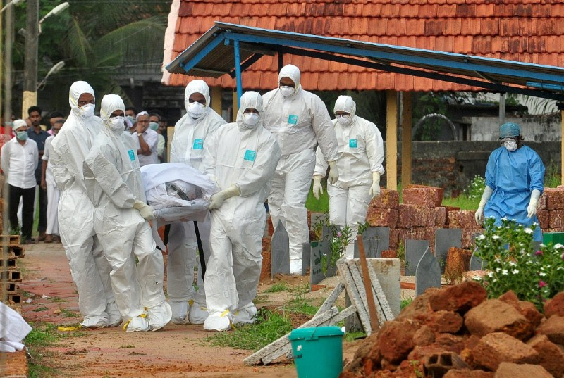 Doctors and relatives wearing protective gear carry the body of a victim, who lost his battle against the brain-damaging Nipah virus, during his funeral at a burial ground in Kozhikode, in the southern Indian state of Kerala, India, May 24, 2018. Credit: Reuters/Stringer