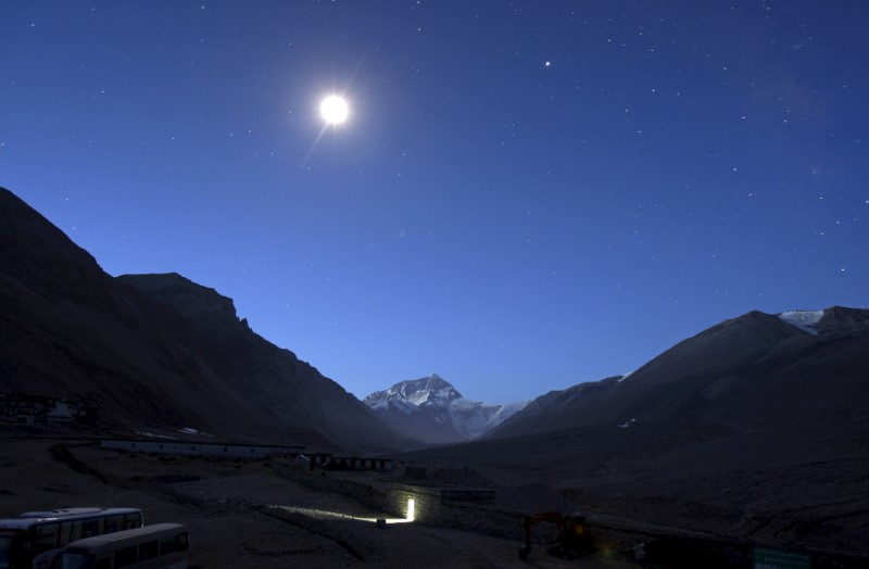The first light of dawn illuminates Mount Everest as the moon shines above and a toilet block is seen in the foreground in the Tibet Autonomous Region, China, April 29, 2008. Credit: Reuters/David Gray/Files