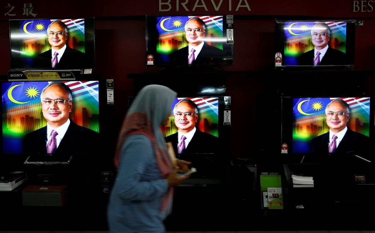 A woman passes a live telecast of Malaysia's former Prime Minister Najib Razak addressing the nation on the dissolution of Parliament at a electronics shop in Port Klang, Malaysia April 6, 2018. Credit: Reuters/Lai Seng Sin