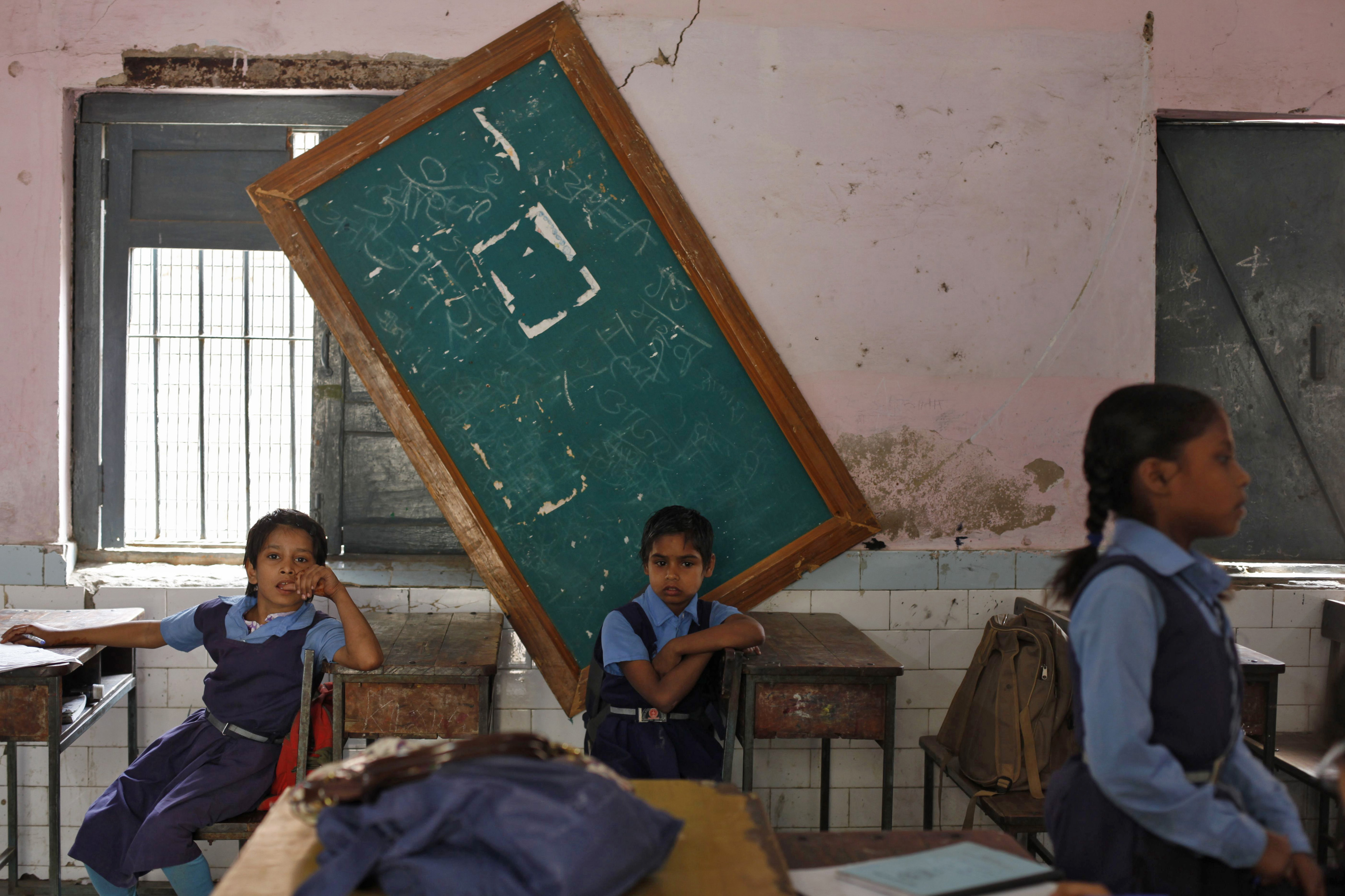 Schoolgirls sit inside their classroom before collecting their free mid-day meals, being distributed by a government-run primary school, in New Delhi May 8, 2013. India may soon pass a new law to give millions more people cheap food, fulfilling an election promise of the ruling Congress party that could cost about $23 billion a year and take a third of annual grain production. The National Food Security Bill, which aims to feed 70 percent of the population, could widen India's already swollen budget deficit next year, increasing the risk to its coveted investment-grade status.