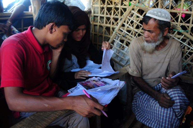 Bangladesh Red Crescent Society staff at a Rohingya refugee camp in Cox's Bazar, Bangladesh take down messages to be sent to the refugeesÕ family members in Myanmar June 28, 2018. Credit: Reuters/Zeba Siddiqui