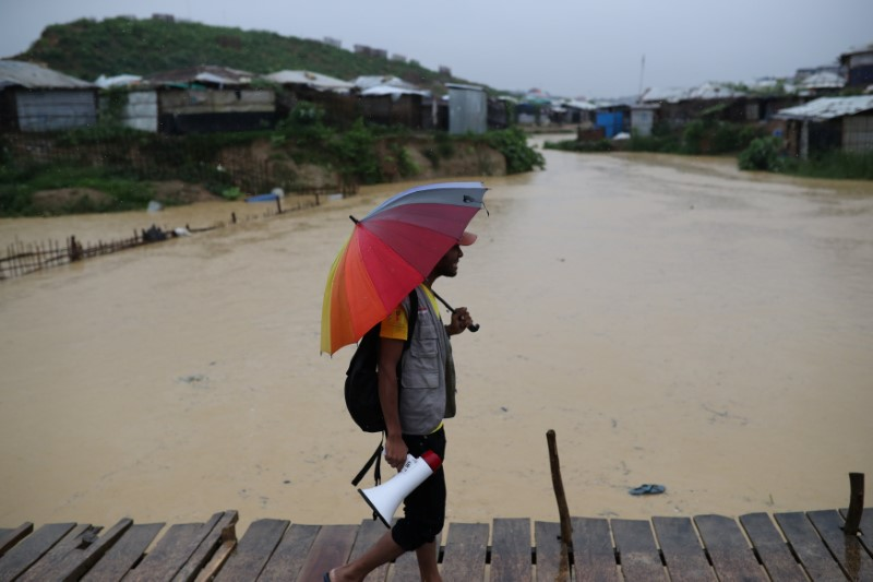 A volunteer of Bangladesh Red Crescent Society Bangladesh walks in the rain to call for the Rohingya refugees who have missing relatives in Myanmar or other countries, in Kutupalong camp in Cox's Bazar, Bangladesh July 4, 2018. Credit: Reuters/Mohammad Ponir Hossain