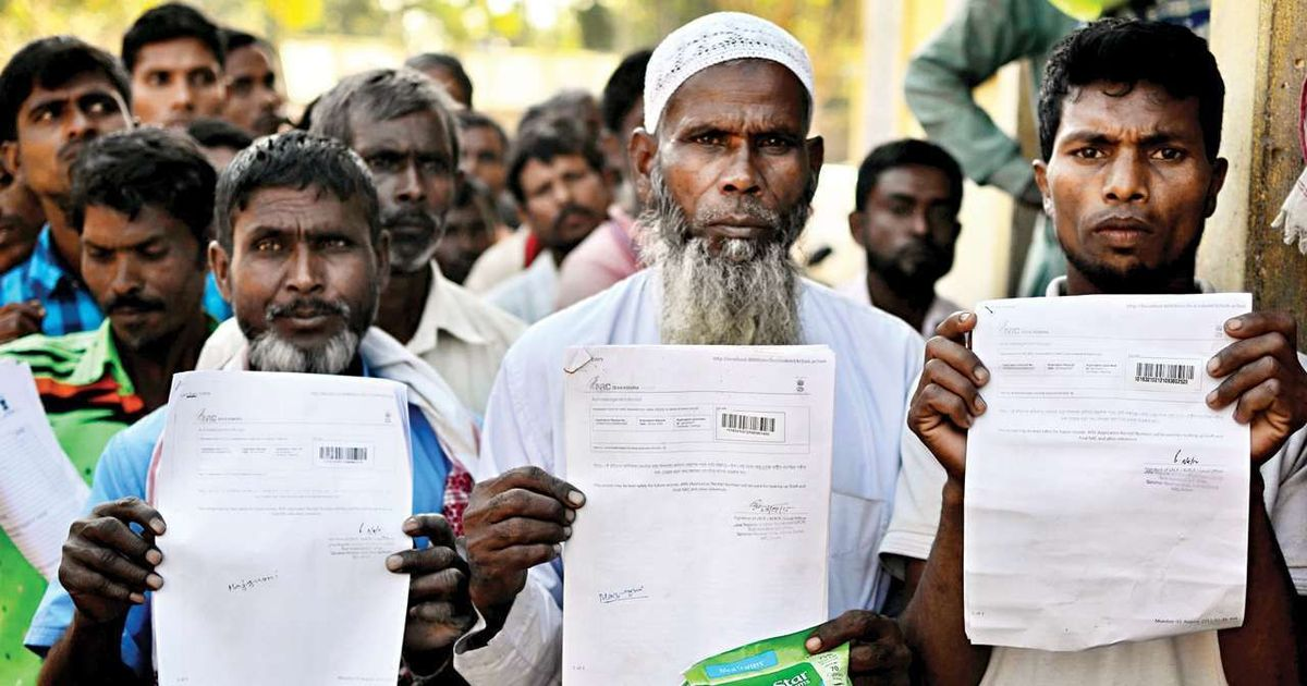 People show their acknowledgement receipts after checking their names in a draft for National Register of Citizens, in Guwahati. Credit: PTI/Files