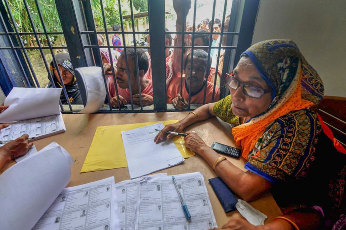 People wait in a queue to check their names on the final draft of National Register of Citizens at an NRC Seva Kendra in Morigaon, Assam. Credit: PTI Photo