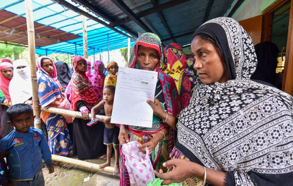 People wait to check their names on the final draft of the state's National Register of Citizens after it was released, at an NRC Seva Kendra in Nagaon on Monday, July 30, 2018. Credit: PTI