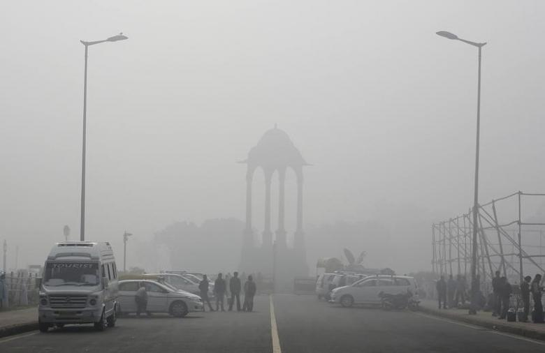Vendors selling drinks stand beside vehicles near the India Gate war memorial on a smoggy day in New Delhi February 1, 2013. Credit: Reuters/Adnan Abidi/Files