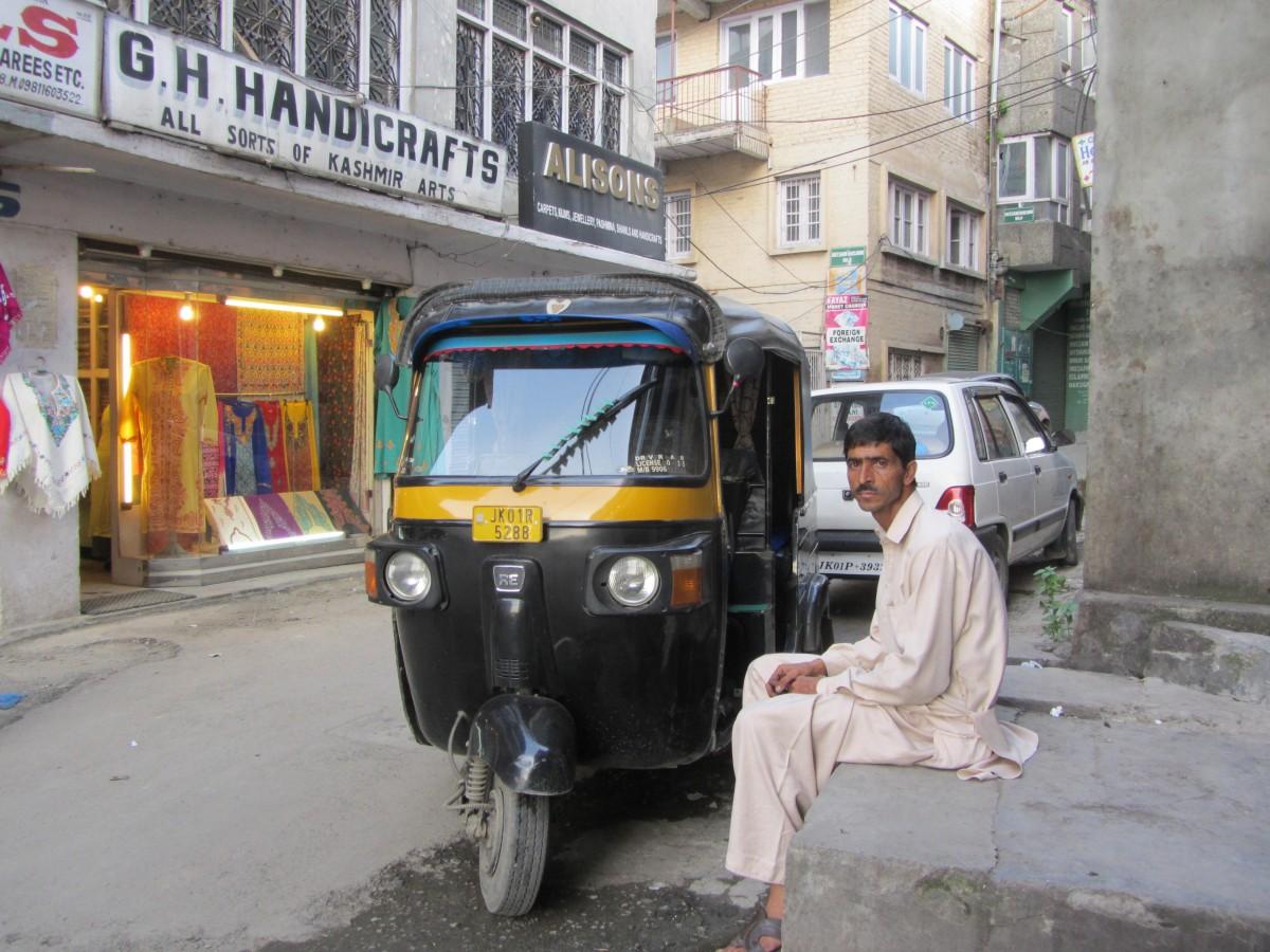 Ajaz waits for a passenger opposite a handicrafts outlet in Srinagar.