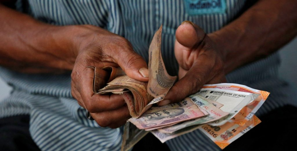 An attendant at a fuel station arranges Indian rupee notes in Kolkata, August 16, 2018. Credits: Reuters/Rupak De Chowdhuri/File Photo