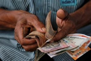 Rupee Hits a Record Low, Dealers Say RBI Intervention Mild