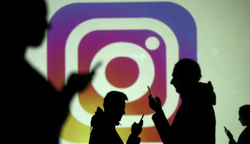 Silhouettes of mobile users are seen next to a screen projection of Instagram logo in this picture illustration taken March 28, 2018. Credits: Reuters/Dado Ruvic/Illustration