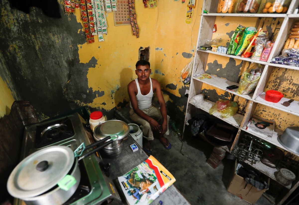 "Raj Narayan, who lost his job as a powerloom operator earlier this year, sits inside his tea shop in Panipat in the northern state of Haryana, India, August 24, 2018. Narayan said he was earning $250 to $300 per month. After losing his job, he opened a tea stall. ""I sent my family back to the village because I am not earning like I used to and it was getting very difficult to support them and bear the expenses,"" Narayan said. Credit: Reuters/Adnan Abidi"
