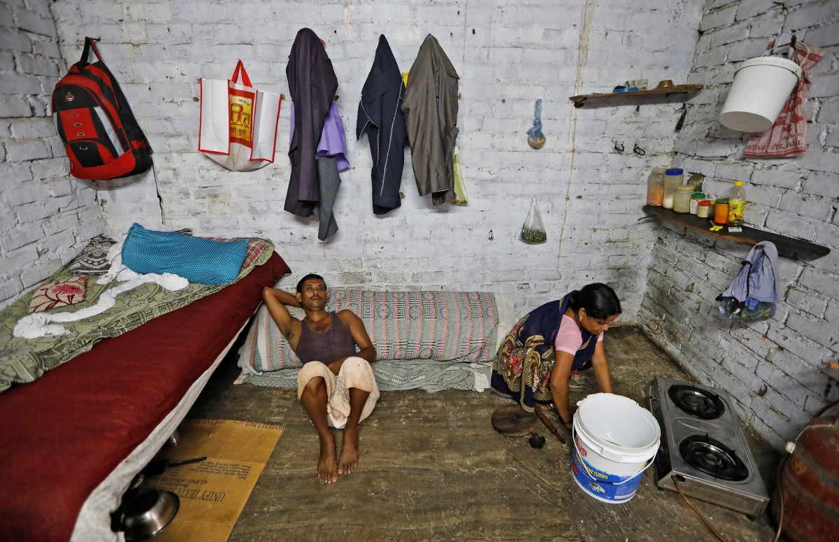 Ram Gati (L) who lost his job as a powerloom operator earlier this year and now works as a packaging labour, lies inside his quarters as his wife cleans the floor, in Panipat in the northern state of Haryana, India, August 29, 2018. Gati said he is not earning much money now. He is thinking of going to a different city to find another job or start a small business from his savings. Credit: Reuters/Adnan Abidi