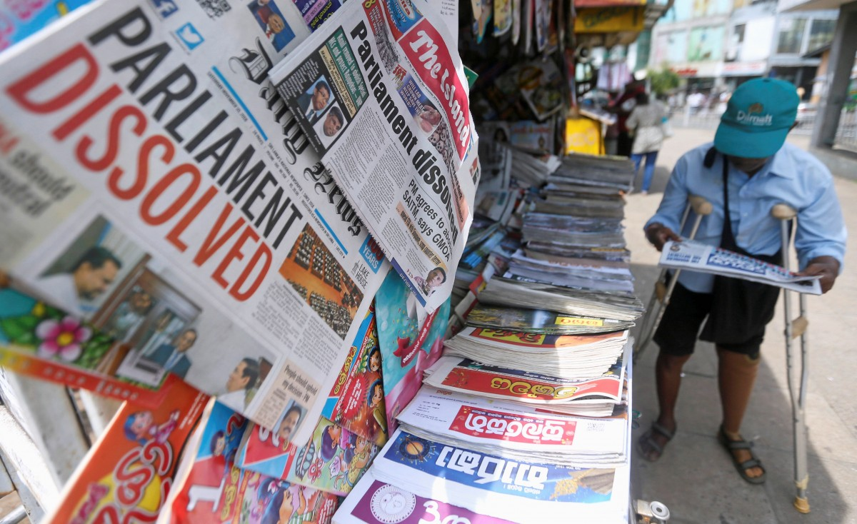 A man reads a newspaper at stall carrying the news of the Sri Lanka's parliament being dissolved, on a main road in Colombo, Sri Lanka November 10, 2018. Credit: REUTERS/Dinuka Liyanawatte