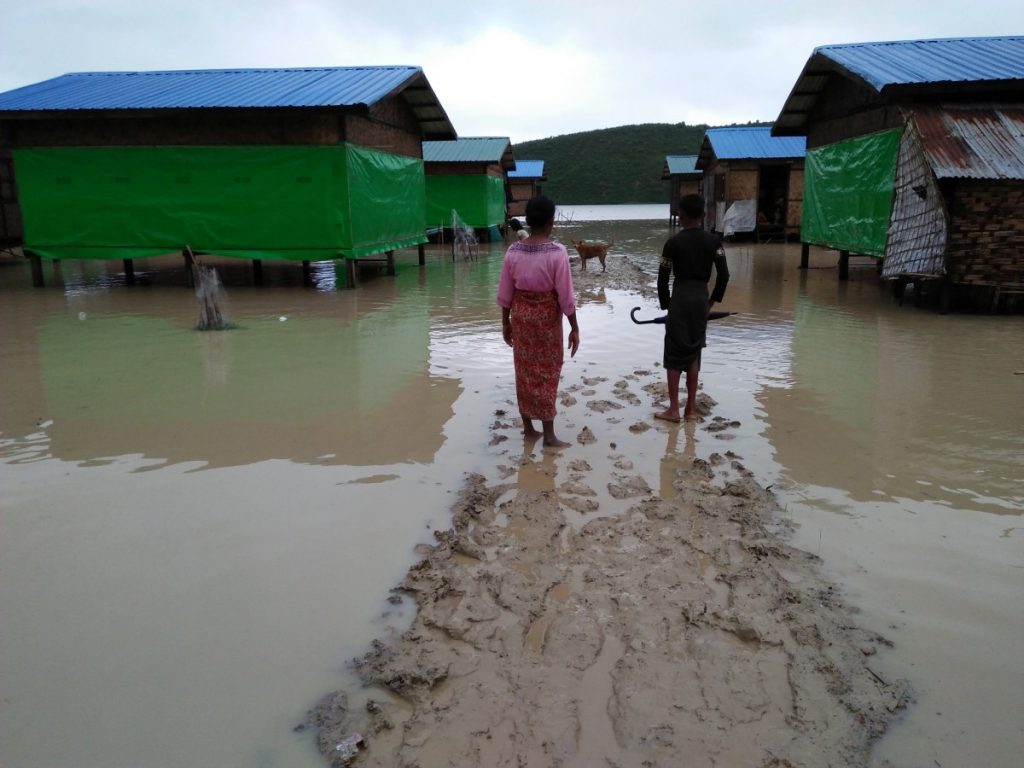 Muslim residents at Taungpaw an internally displaced people's camp walk through the flood to reach the new house built by the Myanmar government in central Rakhine, Myanmar, June 14, 2018. Picture taken June 14, 2018. Credit: REUTERS/ Stringer
