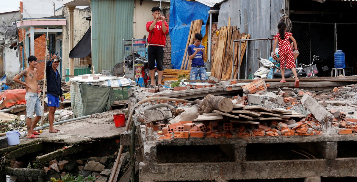 Men stand at their collapsed houses damaged by landslide along Mekong river in Can Tho city, Vietnam December 17, 2018. Picture taken December 17, 2018. Credit: REUTERS/Kham