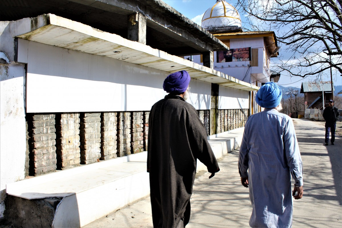 Villagers walk past one of the sites of killings. Credit: Saqib Mir