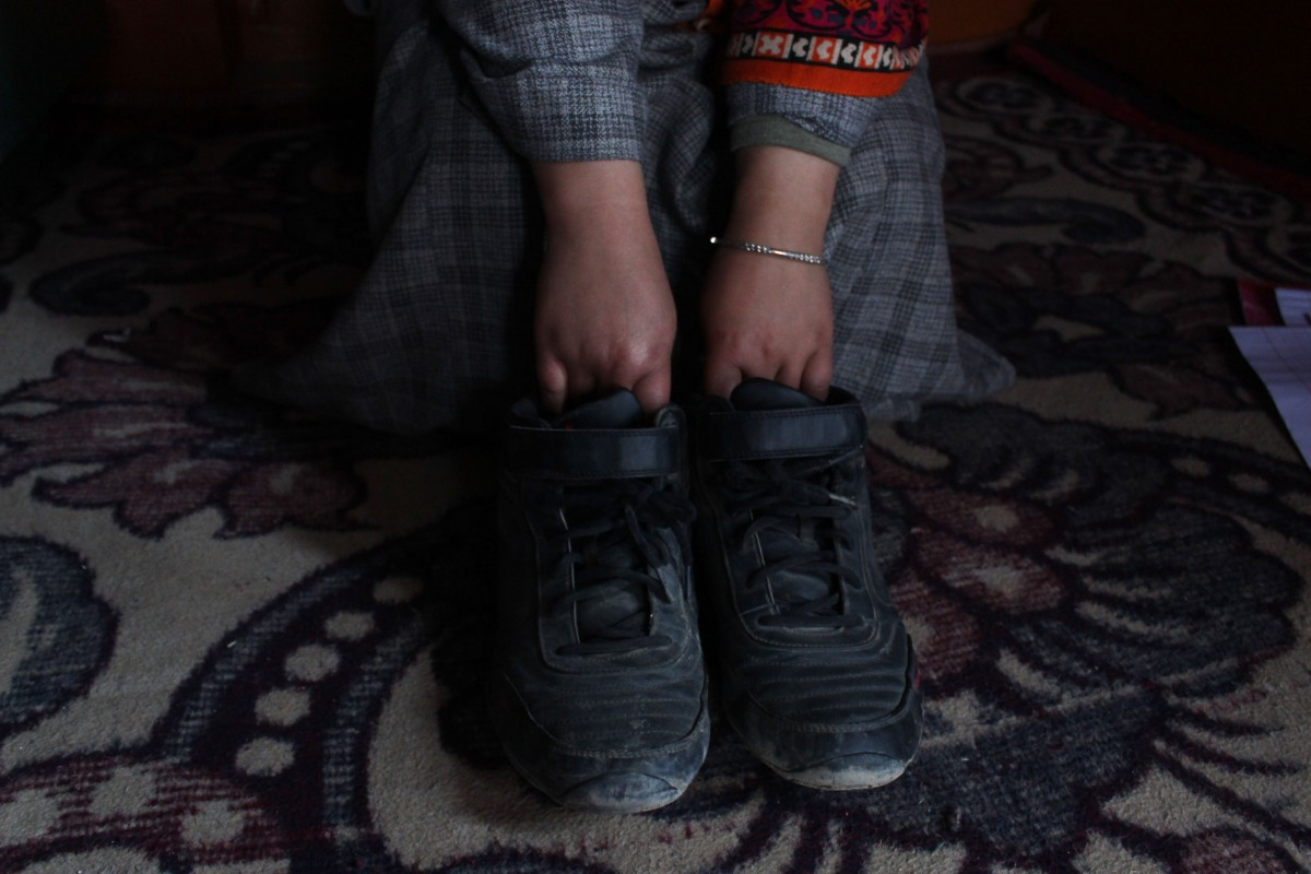 Rizwan's younger sister showing his shoes which he routinely used at home. The family is preserving every belonging of his as a memory. Credit: Waseem Dar