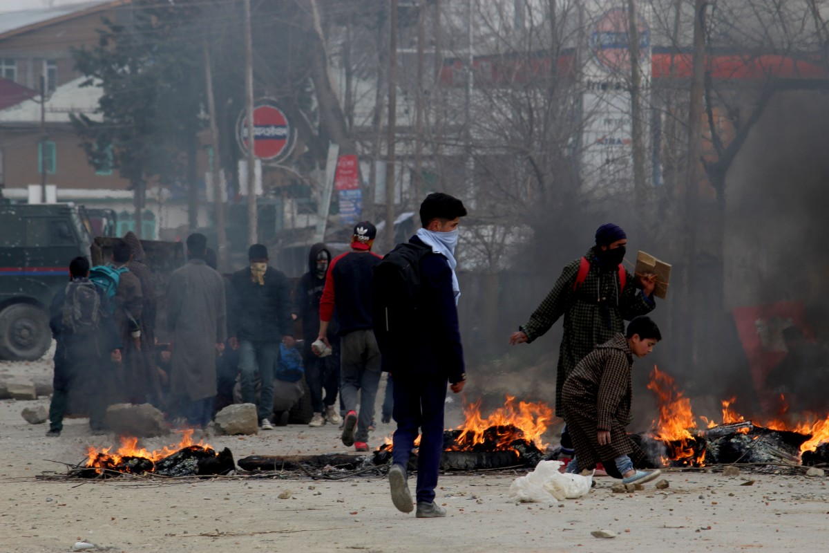 Youth, including some of Rizwan's students, blocking the road with burning logs and rocks to enforce a strike in protest of the killing. Credit: Waseem Dar