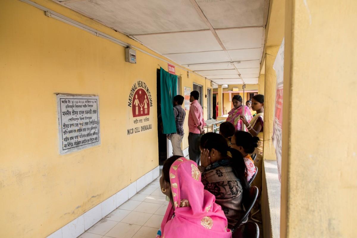 Women wait outside a community health center in Assam. Credit: Andy Ash and Rajan Zaveri/HELM Studio