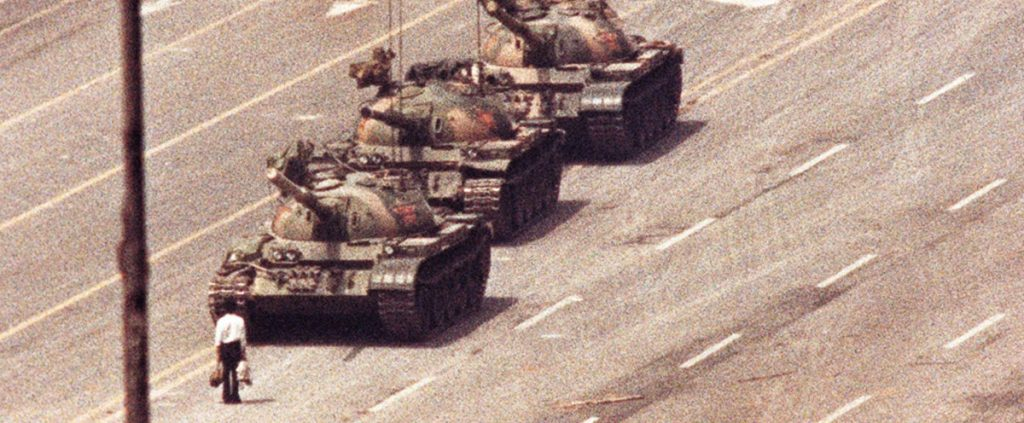 FILE PHOTO: A man stands in front of a convoy of tanks in the Avenue of Eternal Peace in Beijing, China, June 5, 1989. Credit: REUTERS/Arthur Tsang/Files