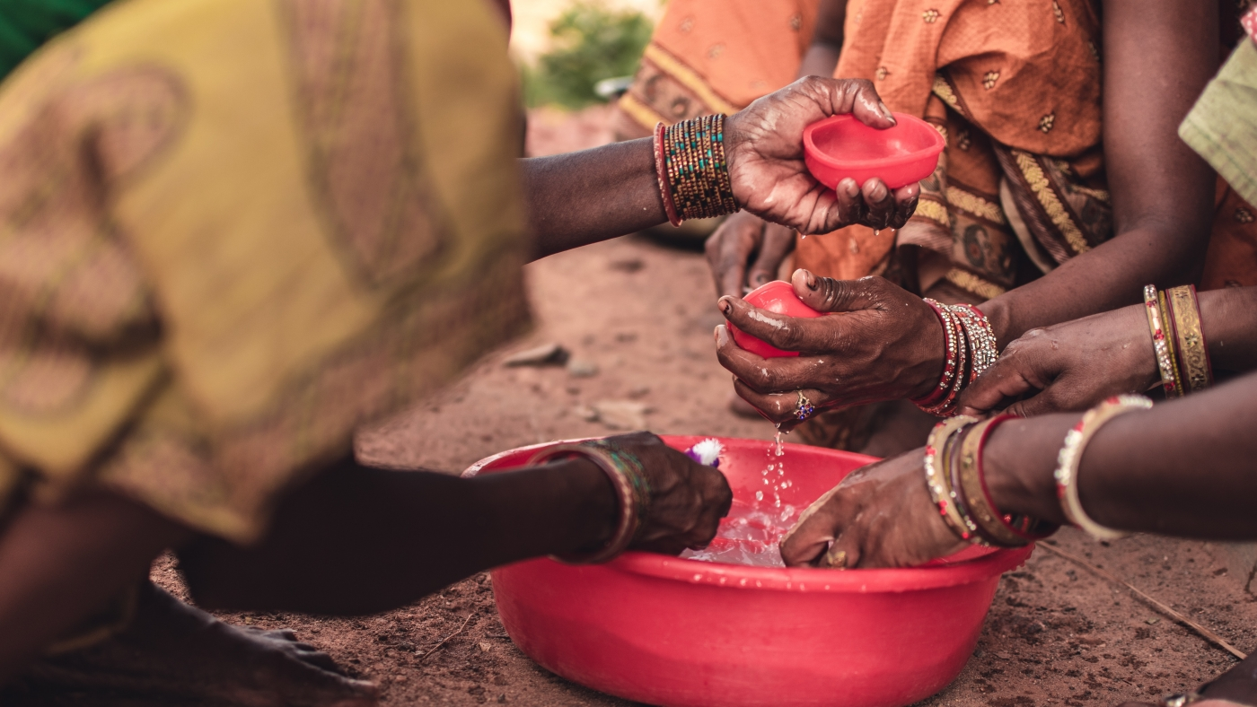 People washing their hands with water in a round red plastic container.
